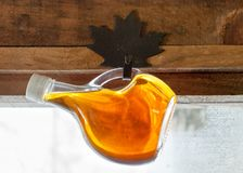 Hanging Bottle of Maple Syrup. Maple Syrup bottle hanging from maple leaf wrought iron hanger on wall royalty free stock image