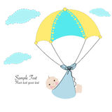 Hanging boy with umbrella baby arrival card Stock Photography