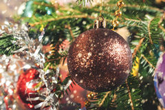 Hanging on branch Christmas balls on the background of Christmas tinsel. Royalty Free Stock Photos