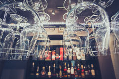 Hanging brandy glasses. On a rack above liquor counter lit by led and down lights with selective focus and vintage blue tone Royalty Free Stock Image