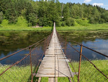 Hanging bridge goes over river Stock Image