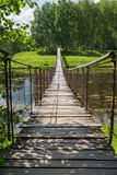 Hanging bridge goes over river Royalty Free Stock Photography