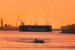 Hanging bridge and oarsmen at sunset Royalty Free Stock Photo