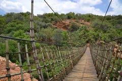 Hanging bridge. An old narrow hanging bridge made from wood and sails Stock Photos