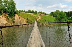 Hanging bridge over the little river Stock Image