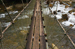 Hanging bridge over waterfall Stock Images