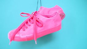 Hanging bright colored sneakers. Fashion woman trendy trainers. Stylish hipster plimsole bright pink blue color sneakers. Minimal pop art concept. Psychedelic stock video footage