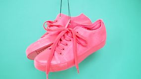 Hanging bright colored sneakers. Fashion woman trendy trainers. Stylish hipster plimsole bright pink turquoise color. Sneakers. Minimal pop art concept stock video