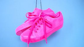 Hanging bright colored sneakers. Fashion woman trendy trainers. Stylish hipster plimsole bright pink blue color sneakers. Minimal pop art concept . psychedelic stock video footage