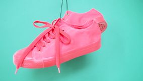 Hanging bright colored sneakers. Fashion woman trendy trainers. Stylish hipster plimsole bright pink turquoise color. Sneakers. Minimal pop art concept stock footage