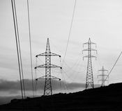 Hanging cables and electric towers Stock Photography