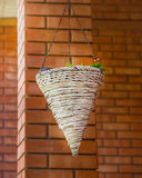 Hanging cache-pot against a red brick wall. Stock Photo