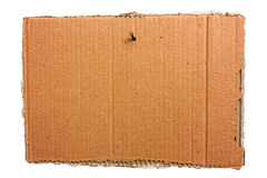 Hanging cardboard sheet - clipping path. Empty signboard of ripped cardboard sheet, hanging with nail, blank notice of torn corrugated pasteboard, isolated stock photography