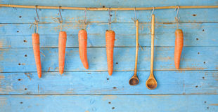 Hanging carrots and old wooden spoons Royalty Free Stock Photography