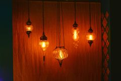 Hanging from the ceiling lamps in Oriental style. Hanging from the ceiling burning lamps in Oriental style, warm light Royalty Free Stock Photo