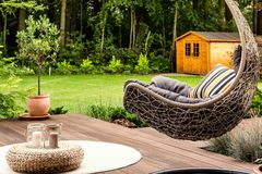 Hanging chair in the garden. Pouf on white round rug next to a hanging chair in the garden of a house stock photo