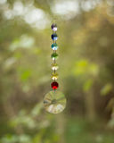 Hanging chakra crystals. Multifaceted colourful chakra crystals hanging in front of a garden stock image