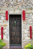 Hanging Chili Peppers Adorning a Stone Wall Royalty Free Stock Photo