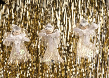 Hanging Christmas angels and tinsel. Three Christmas angels hanging in front of a tinsel background Stock Images