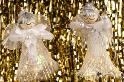 Hanging Christmas angels and tinsel. Three Christmas angels hanging in front of a tinsel background Royalty Free Stock Image