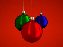 Hanging christmas balls. Three hanging Christmas balls on a red background Stock Photography