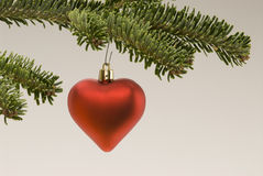 Hanging Christmas heart on white background. Hanging red Christmas heart on white background. Christmas tree stock photo