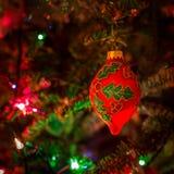 Hanging Christmas tree bauble among shiny background lights Royalty Free Stock Image