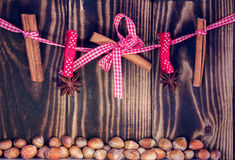 Hanging cinnamon and anises on a rope and hazelnuts on a wooden background Royalty Free Stock Image