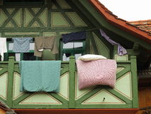 Hanging clothes and bedding over balcony Stock Images