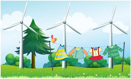 Hanging clothes in front of the windmills. Illustration of the hanging clothes in front of the windmills Stock Photos