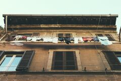 Hanging Clothes and Pants Beside Brown Building royalty free stock photography