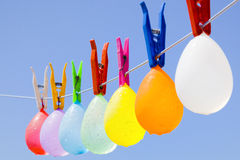 Hanging colored balloons. Selective focus on a bunch of wet colored water filled balloons hanging on a clothesline with a blue sky as background Stock Photography