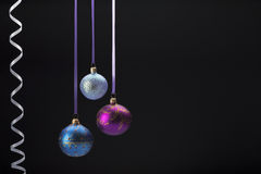 Hanging colorful christmas balls on black Royalty Free Stock Images