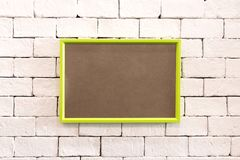 Hanging colorful photo frame on brick wall in loft concept style. Blank vivid border for your design or show at gallery room. Hanging colorful photo frame on royalty free stock photo