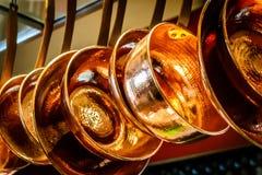 Hanging copper pots, pans, saucepans. In open shelves in open concept kitchen Stock Images