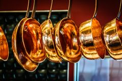Hanging copper pots, pans, saucepans. In open shelves in open concept kitchen Royalty Free Stock Photography