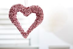 Hanging decorative heart. In a bright interior room royalty free stock photography