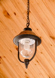 Hanging dirty lantern with cobweb and dead insects. Hanging dirty metallic lantern with dead fried insects on it against wooden background. Old outdated Royalty Free Stock Photo