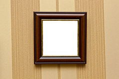 Hanging empty photoframe. On a retro wall with striped wallpapers royalty free stock photos