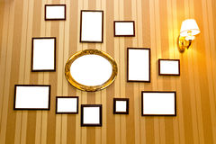 Hanging empty photoframes. On a retro wall with striped wallpapers royalty free stock images