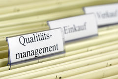 Hanging file Qualitätsmanagement. Close-up hanging files with tab Qualitatsmanagement what means Quality Management in German Royalty Free Stock Photo