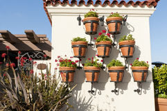 Hanging flower pots. Decorative clay flower pots hanging on a building wall Royalty Free Stock Image