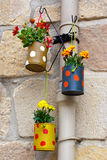 Hanging flowerpots made with cans. Royalty Free Stock Photo