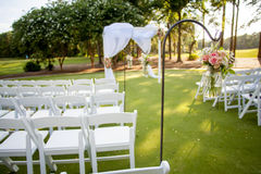 Hanging flowers for wedding. Chairs and arbor with hanging flowers for wedding, focus on flowers in jar Stock Images