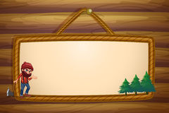 A hanging frame with a lumberjack and three pine trees Royalty Free Stock Photography