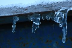 Hanging icicles on the cornice. Hanging frozen icicles on the cornice royalty free stock images