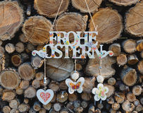 Hanging getting Happy Easter in German in front of firewood background. Rustic style. Decor for home and garden Stock Image