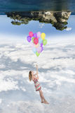 Hanging girl to a group of balloons flying toward a world upside Royalty Free Stock Images