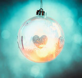 Hanging glass Christmas ball with heart and bokeh lighting. On turquoise blue background stock images