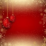 Hanging glittery baubles on a gold confetti background. With snowflakes Stock Photo